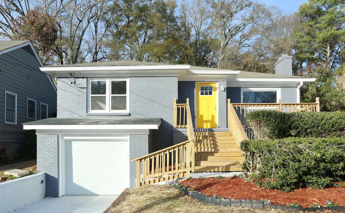 Gray house with bright yellow door and stairs leading down to driveway leading to white garage door.
