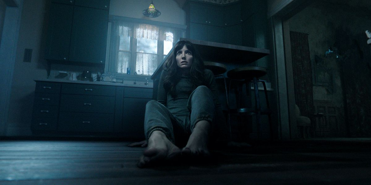 Annabelle Wallis sits wide-eyed on the floor of a dark kitchen in Malignant