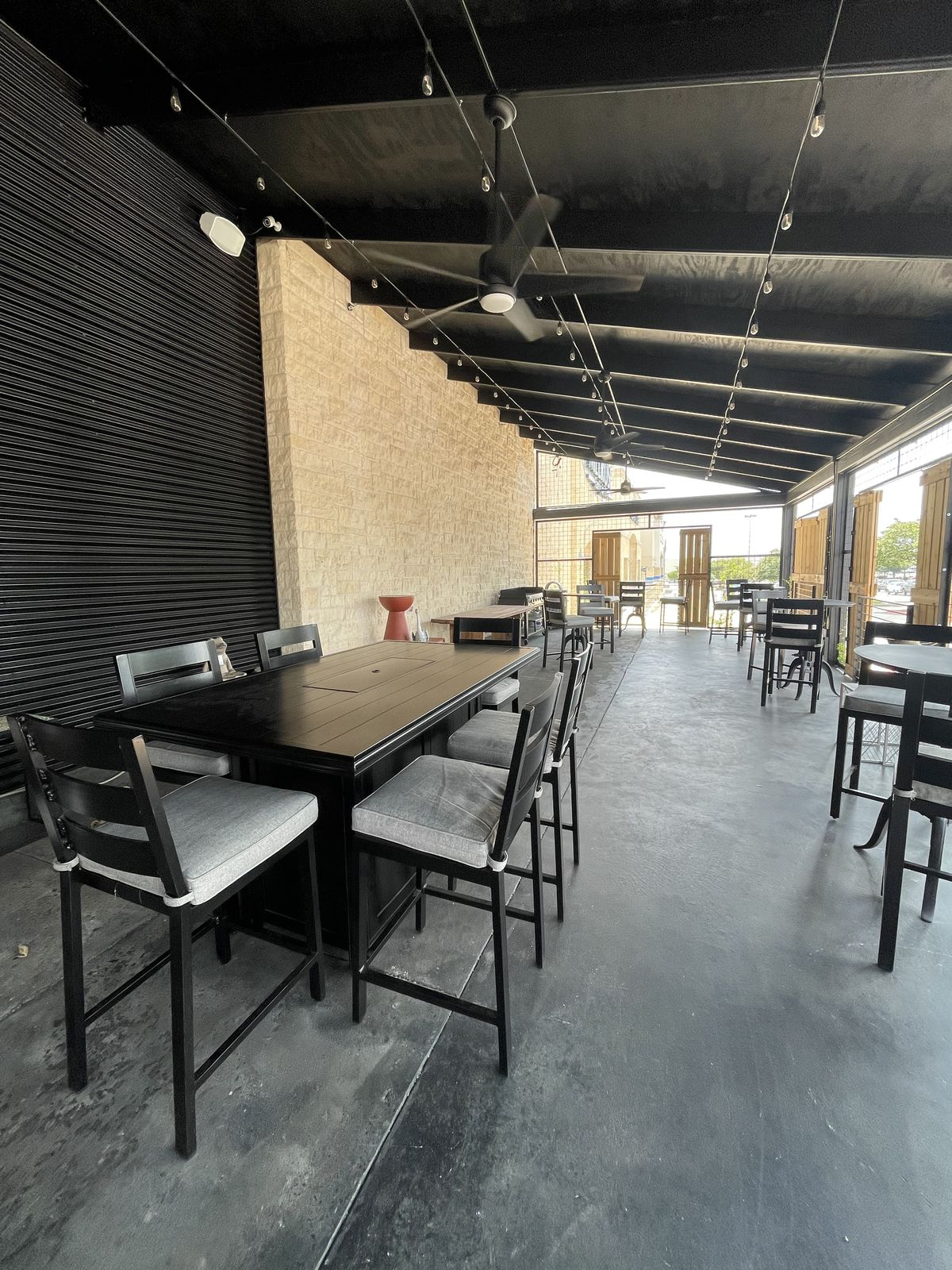 An outdoor dining area with black tables and chairs and a black awning