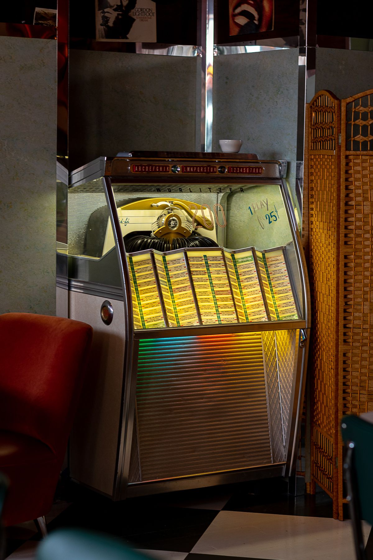 """The jukebox features chrome finishes on the exterior with beige linoleum panels and paint on the window that reads """"1 Play for 25 cents."""""""