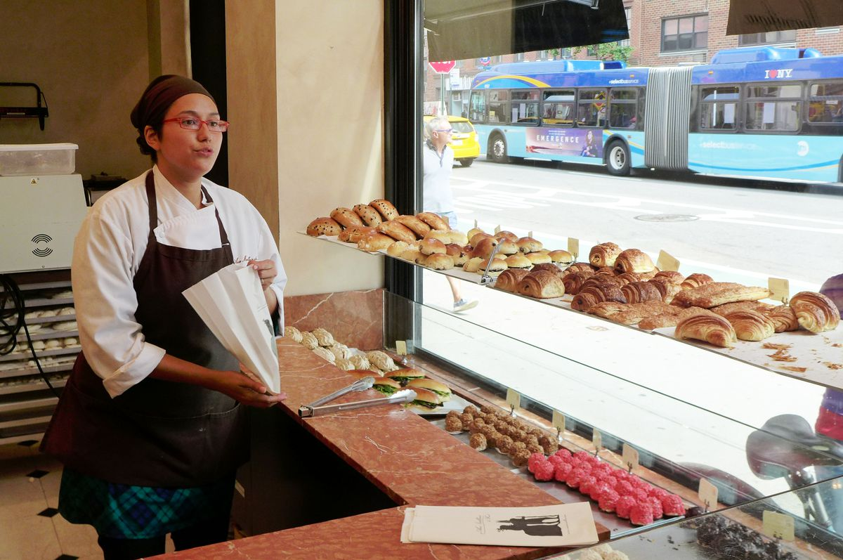 A woman in a white uniform with brown apron and cap stands before a window full of pastries...