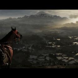 A samurai warrior on horseback stands on a hill overlooking rice paddies.