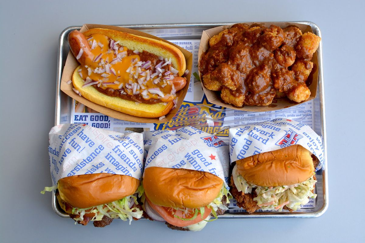 Hollywood burger's food shown on a tray, including a cheeseburger, chili tots, a hot dog, and more, from above.