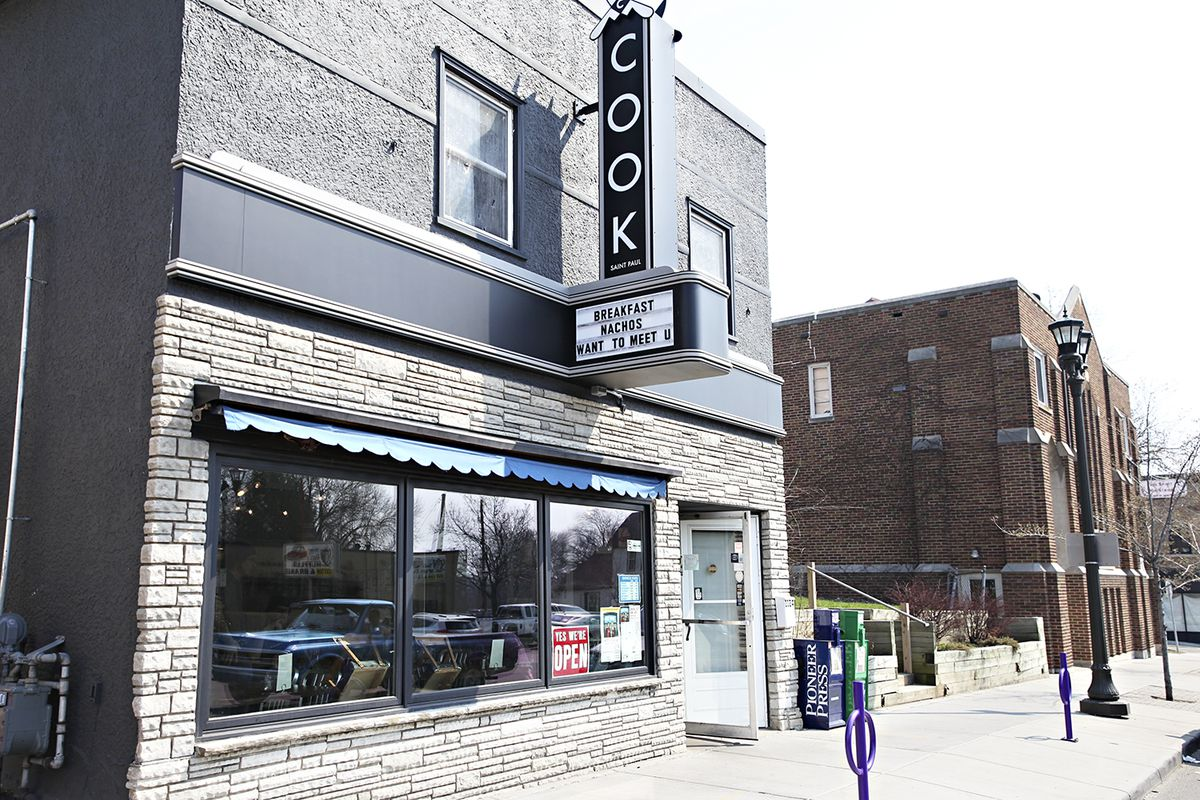 The exterior of Cook with a large vertical sign and open storefront windows