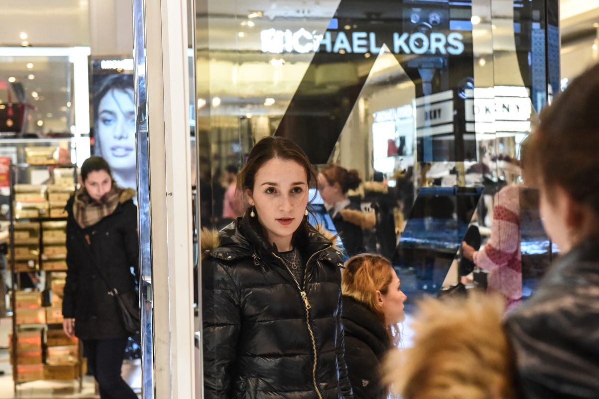 Holiday shopper looks at herself in a department store mirror