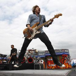 Foreigner bassist Jeff Pilson jumps during the band's performance before the the NASCAR Sprint Cup Series auto race at Texas Motor Speedway Saturday, April 14, 2012, in Fort Worth, Texas.