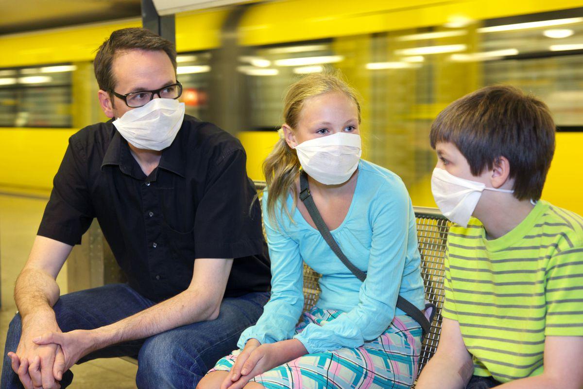 A family on a subway platform wearing hygienic masks.