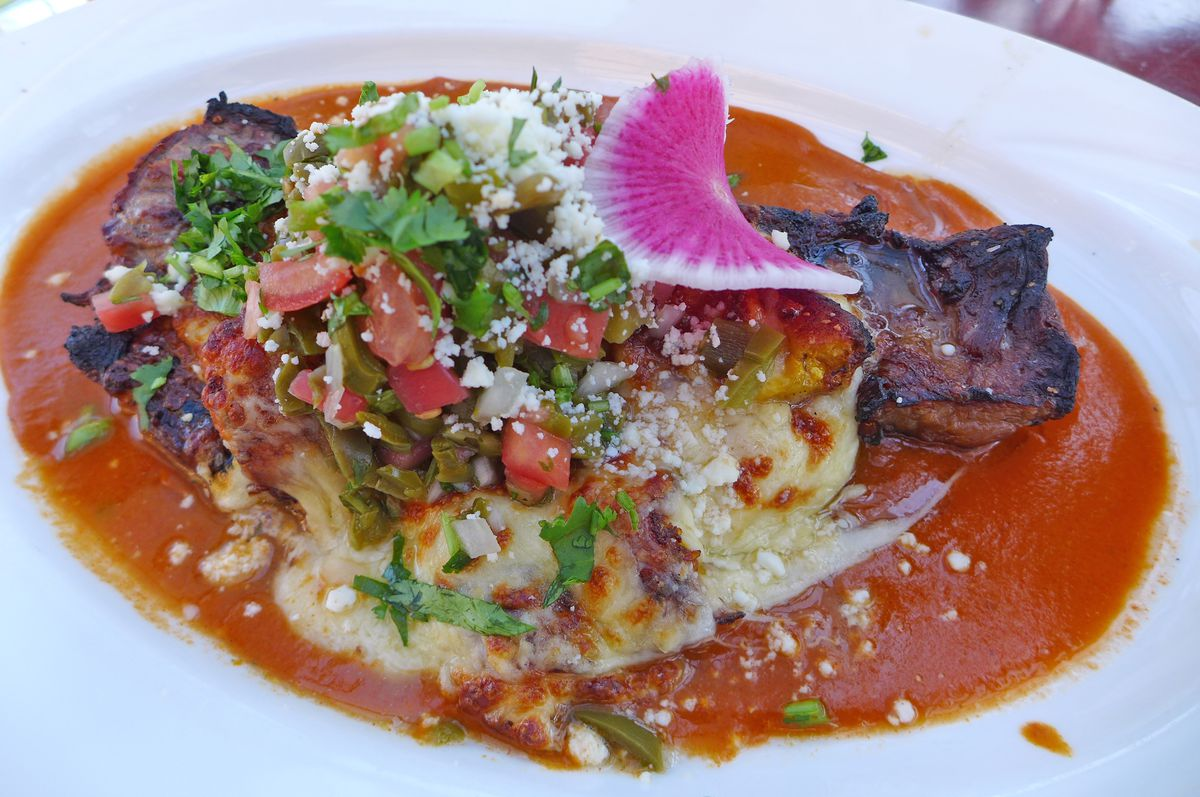A steak covered with grated cheese and vegetables in a pool of yellowish red sauce.