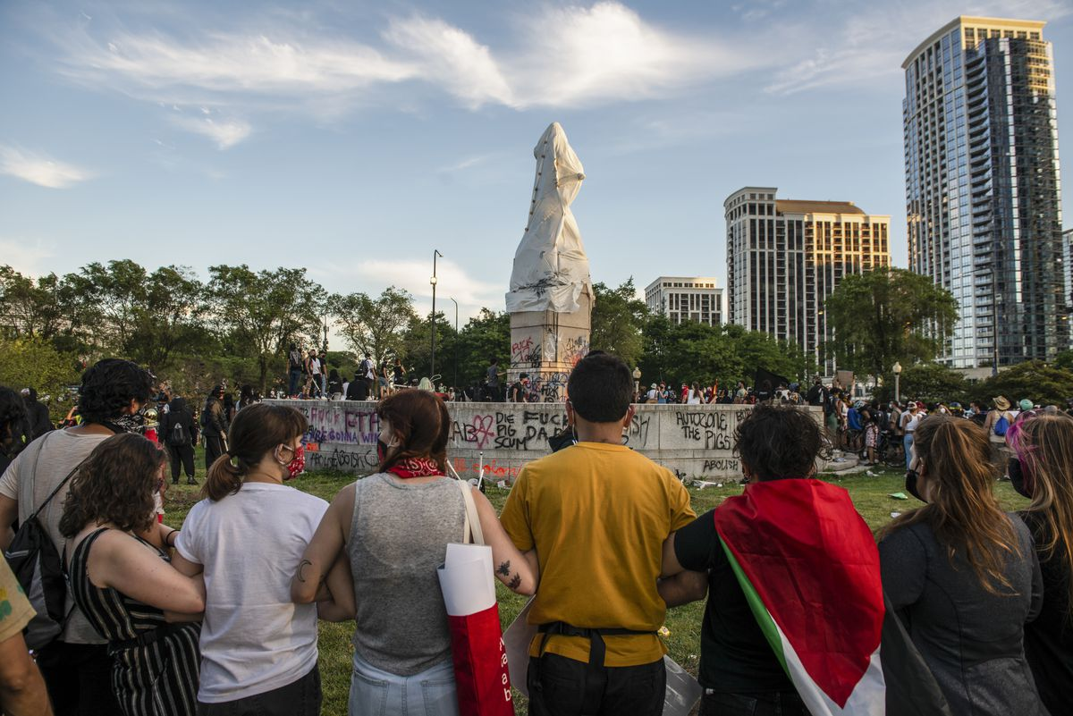 Protesters surround the Christopher Columbus statue in Grant Park on Friday, July 17, 2020.