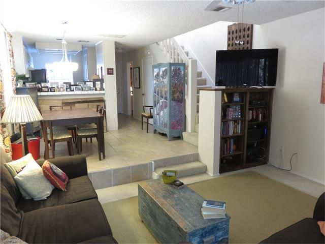 Inside of condo with living room, steps up to dining/kitchen area, stairs to second story, bookcases and other nondescript furniture except for one that looks kind of Asian in the back