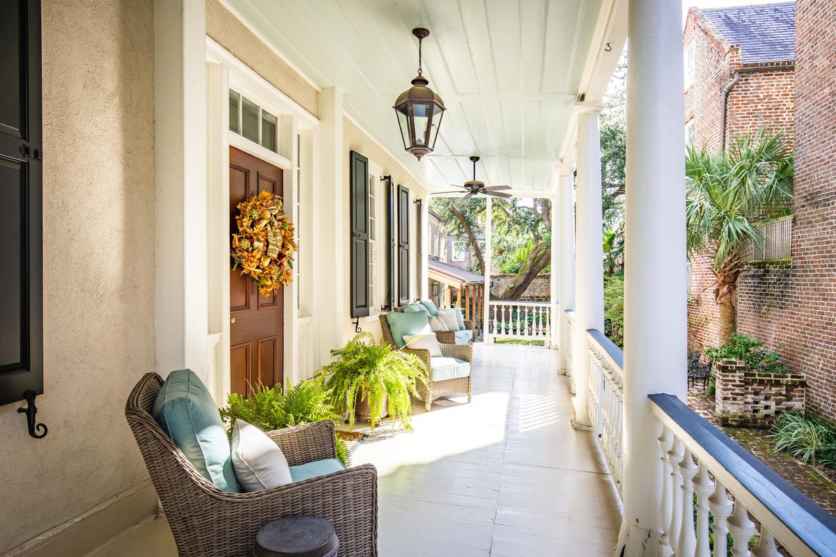 A side view of a covered porch with ferns, wicker furniture, and gas lights.