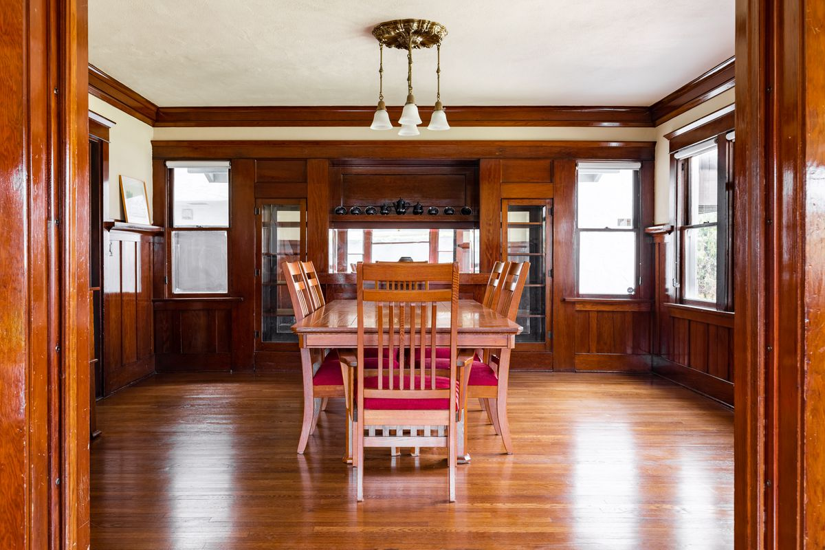 A room with a large table and chairs and cabinets