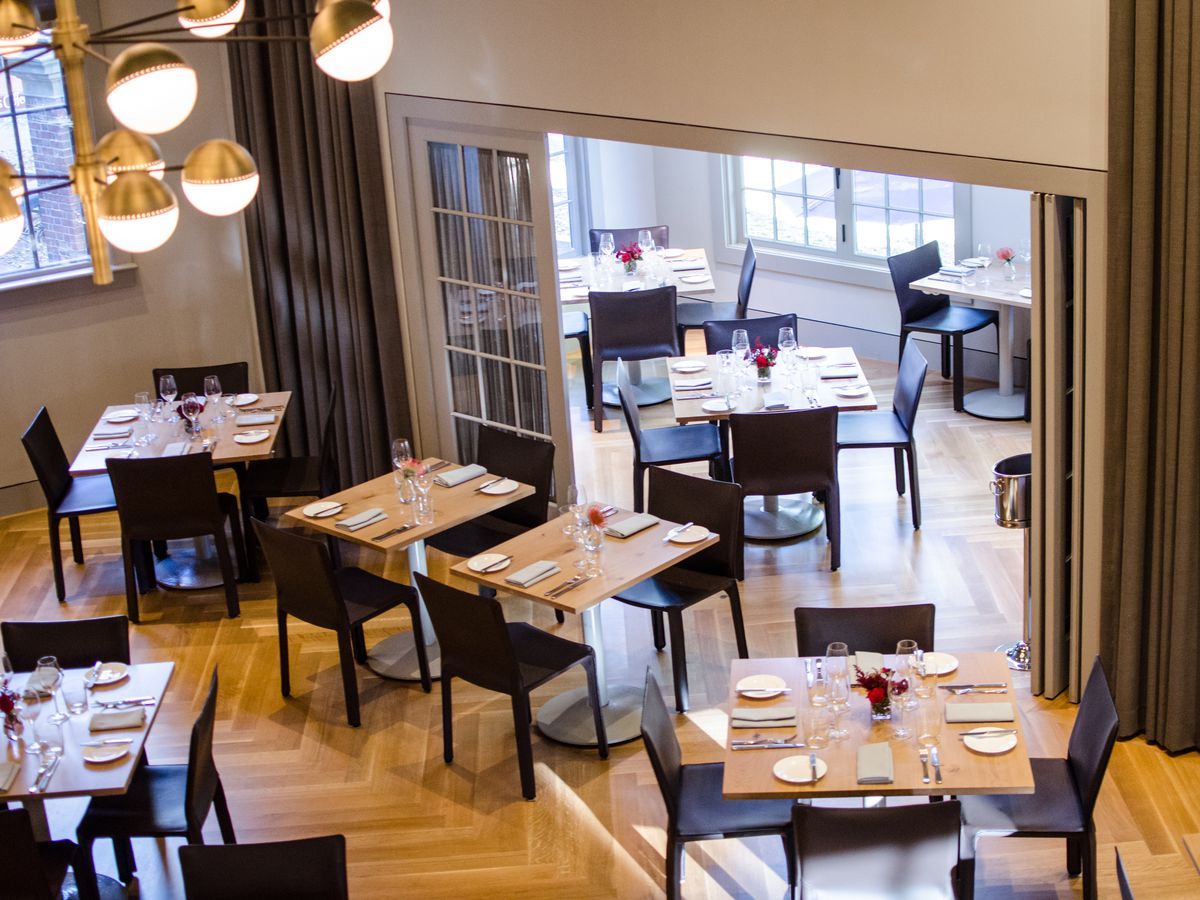 An overhead view of Parsnip's high-ceilinged main dining room, with light wood tables and dark chairs