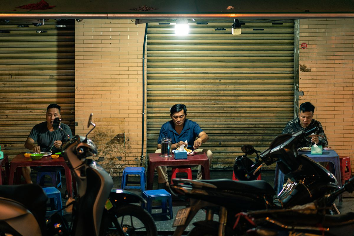 three men sit at small plastic tables and eat food in front of motorcycles