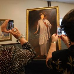 Women take a photo of a painting of Janie Thompson during a memorial service for her at the BYU multi-stake center in Provo on Saturday, June 8, 2013. Thompson was the founder of BYU's internationally touring Young Ambassadors.