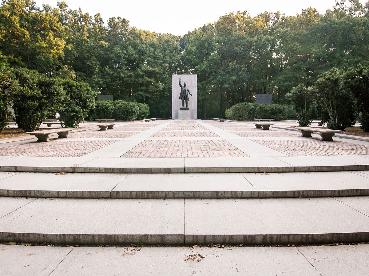 An area on Theodore Roosevelt Island in Washington D.C. There is a courtyard surrounded by trees. In the courtyard is a monument with a statue of a man.