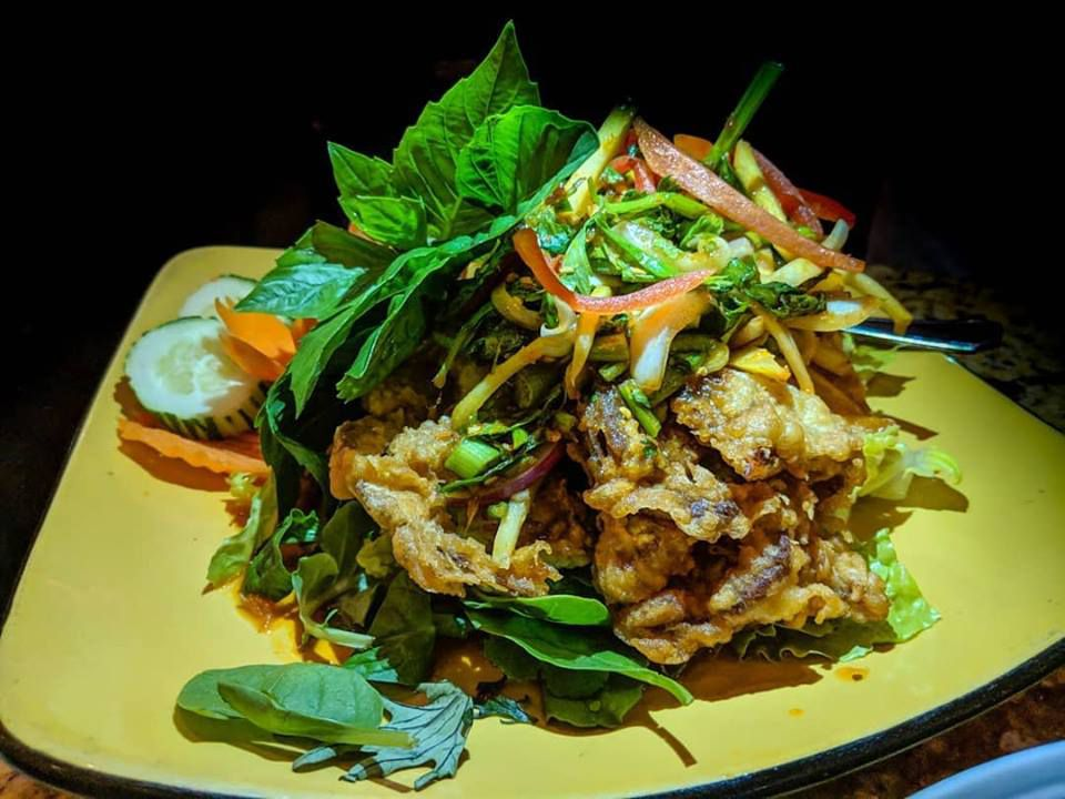 A mountain of fried soft shell crab with greens sits on a square yellow plate on a dark background.