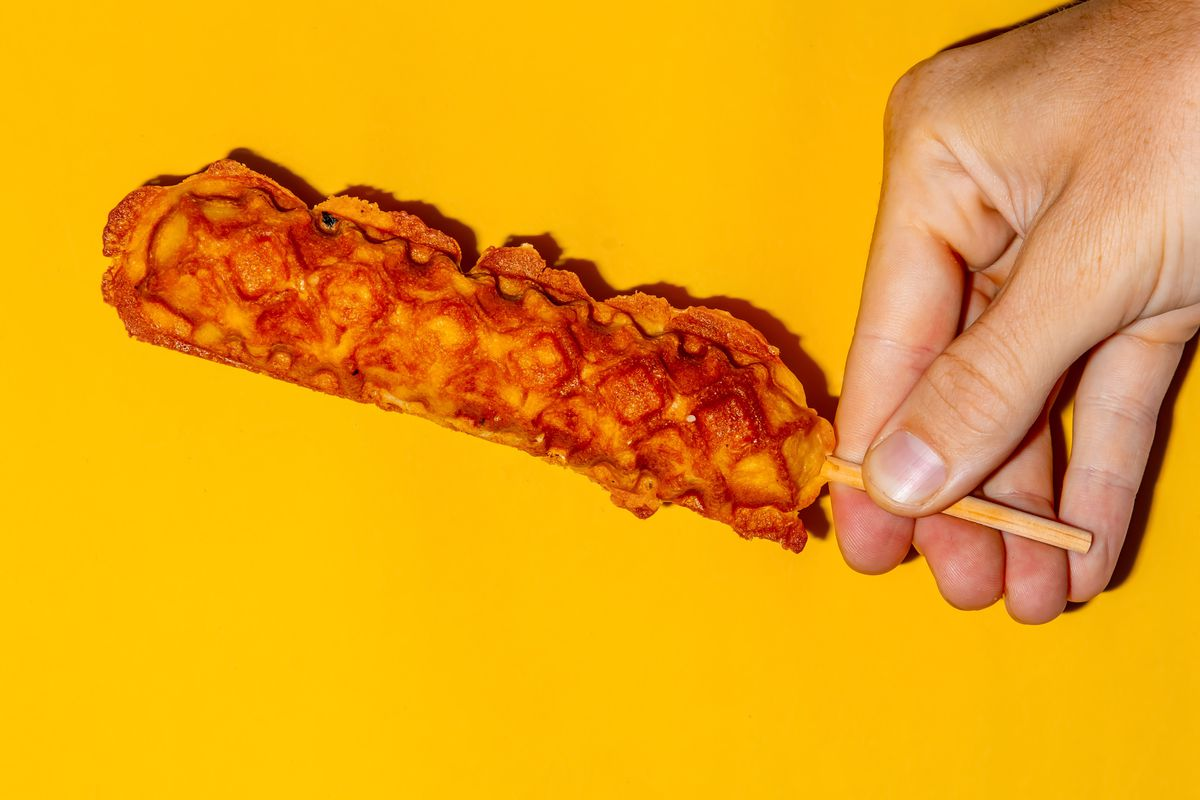 A hand holding a chicken in a waffle on a stick against a yellow background