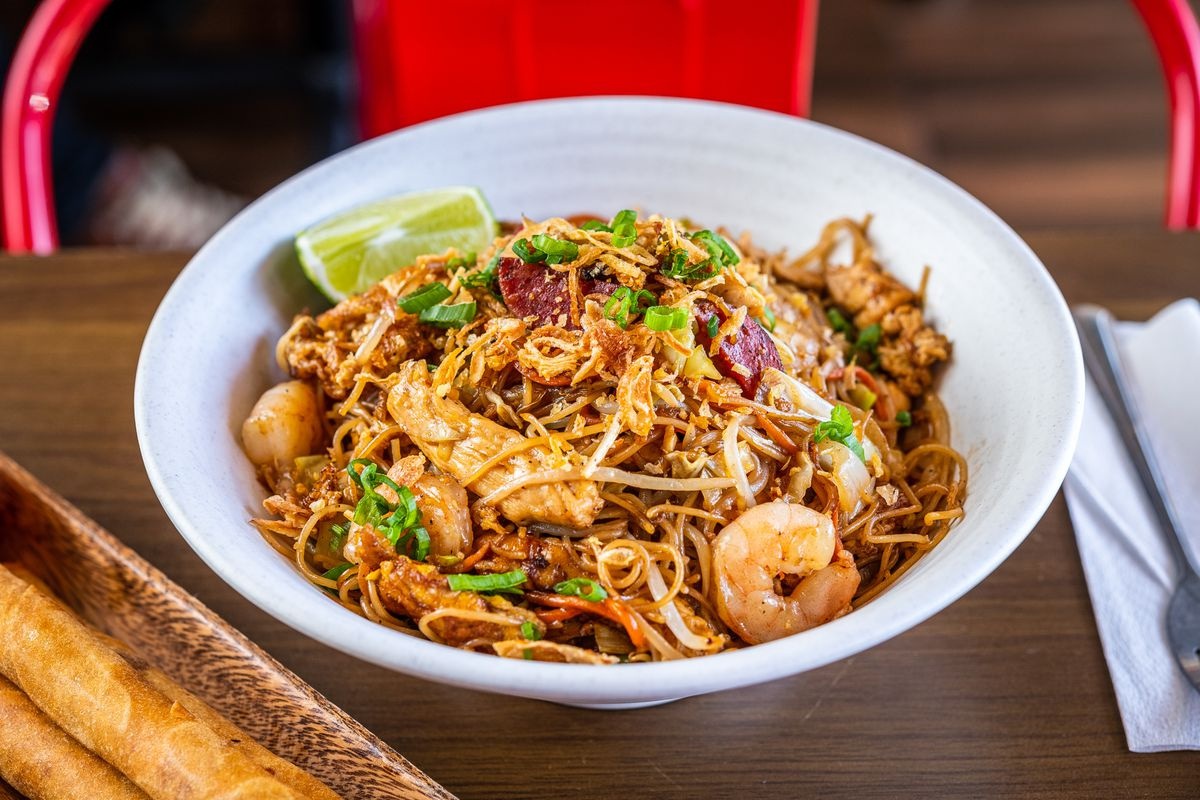 A signature pancit bowl from Kuya Ja's mixes rice noodles with pieces of shrimp, chicken, longganisa sausage, egg, and vegetables.