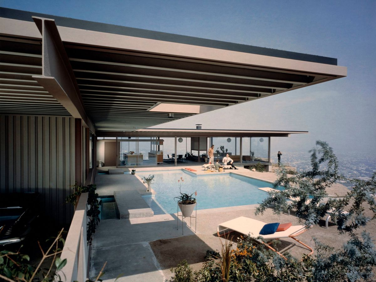 The exterior of the Stahl house in Los Angeles.  There is a swimming pool next to the house with a lounge area. The pool is situated on a cliff edge.