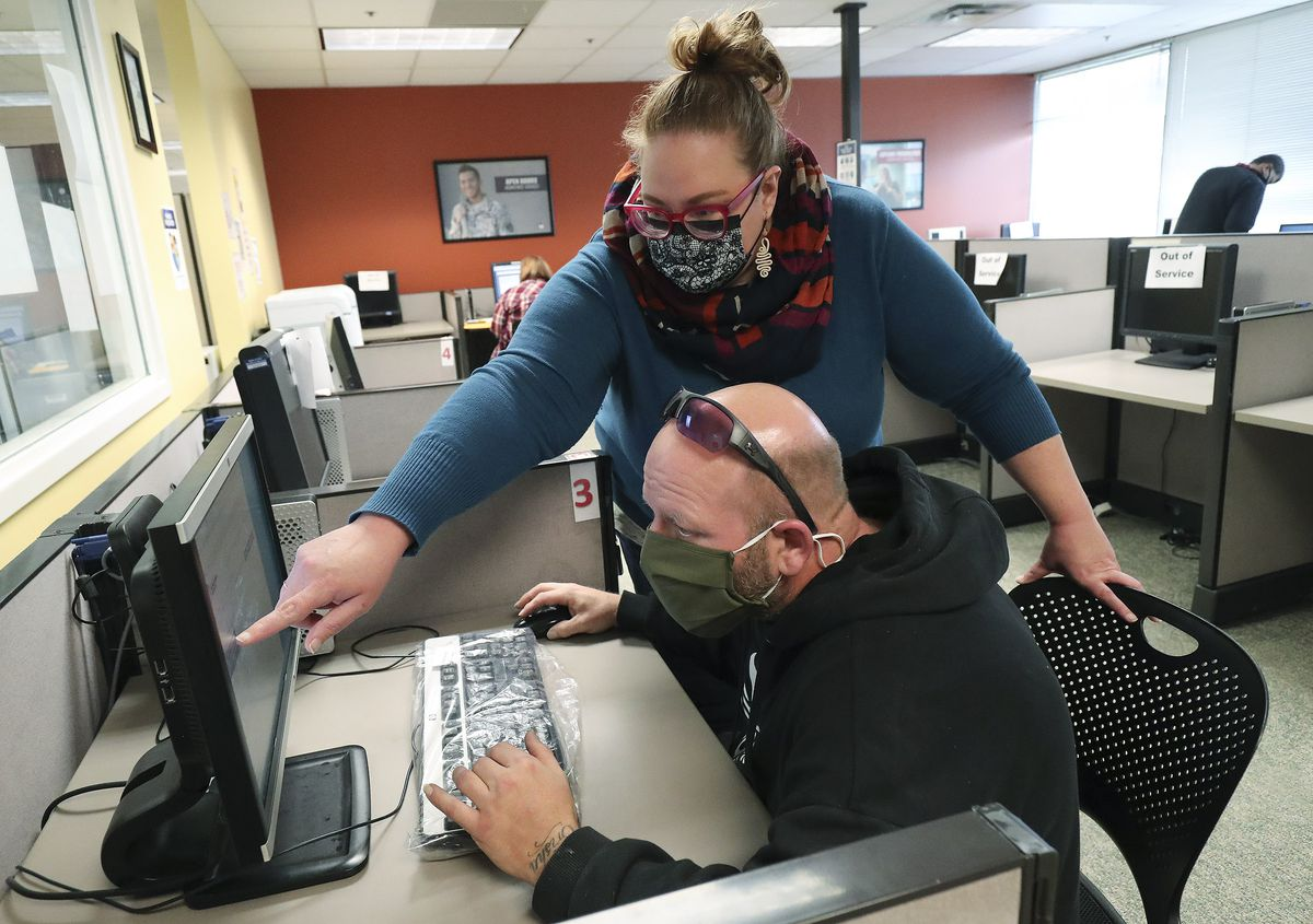 Toby Barrett, seated, gets some help from the Department of Workforce Services' Brooke Coster while looking for a job at the department's office in Salt Lake City on Friday, Dec. 18, 2020.