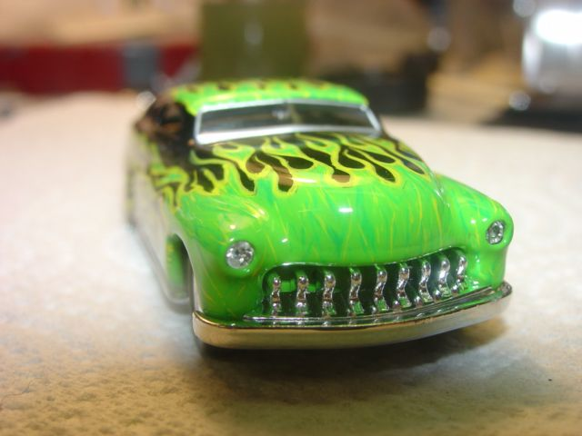 Photo of the front of a custom Hot Wheels muscle car/roadster with painted green flames engulfing the hood.