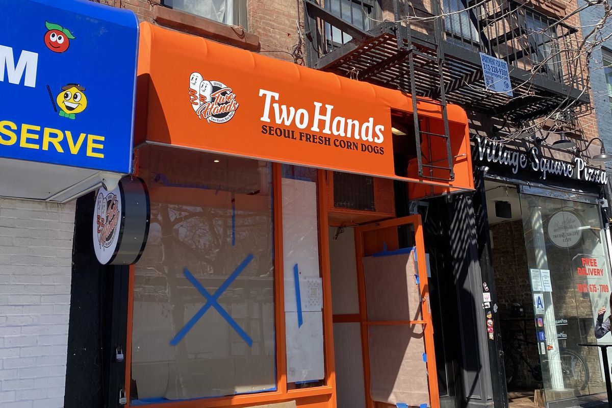A bright orange storefront with brown paper taped over the windows, and an orange awning with white lettering showing the restaurant's title and logo
