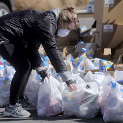 Debbie Jackson grabs bags of foodfrom the Utah Food Bank to hand out in the parking lot of a chapel belonging to The Church of Jesus Christ of Latter-day Saints in Taylorsville on Monday, April 13, 2020. The Utah Food Bank estimates it provided food to around 400 families at this location.