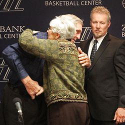 Utah Jazz coach Jerry Sloan hugs Gail Miller as Greg Miller watches after announcing his resignation after being the head coach for the Jazz since 1988.