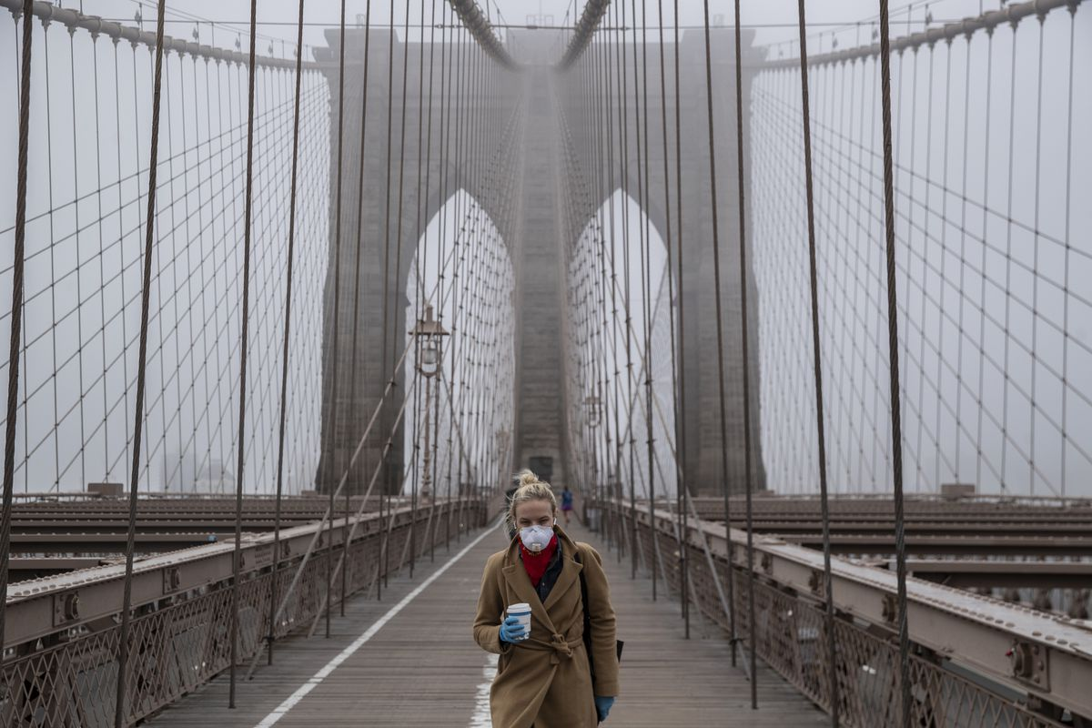 A woman wearing a mask crosses the Brooklyn Bridge in New York City on March 20, 2020.