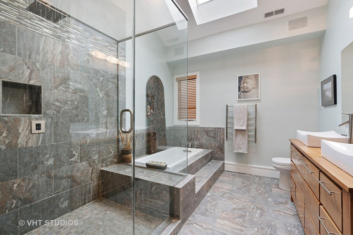 A marble tile bathroom with a glass shower and stepped up bathrub under a skylight near a double vanity.