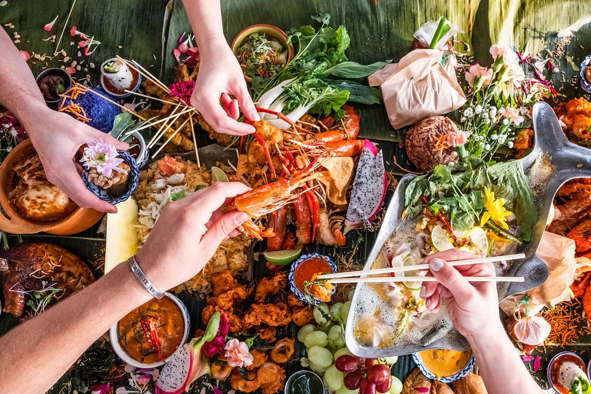 A Thai food feast with lots of colorful dishes on a table from above.