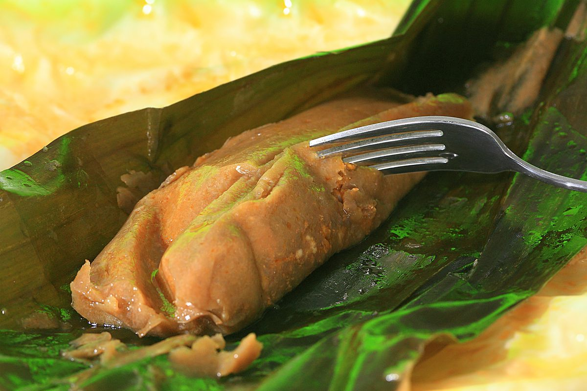 A fork digs into an open pasteles