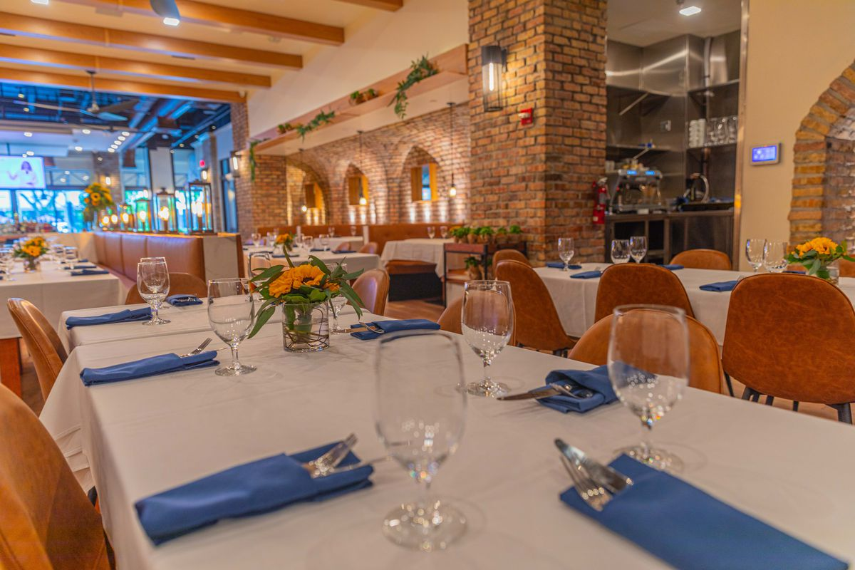 tables with white tablecloths, blue napkins, and yellow sunflowers with brick walls in the background