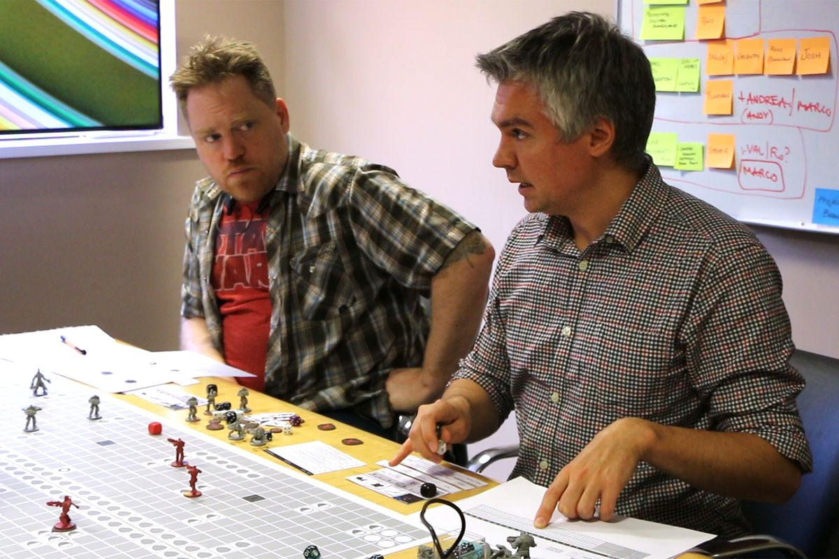 Two men discuss the rules of a board game. On the table is a black and white map with shields on it, some d6 and d10 dice, as well as some Gears of War themed plastic miniatures in white and gray plastic.