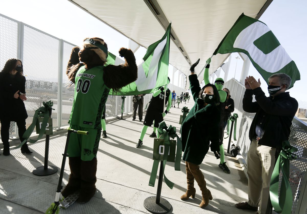 Utah Valley mascot Willy the Wolverine, left, President Astrid Tuminez and others celebrate a new pedestrian bridge connecting UVU with the UTA's FrontRunner station.
