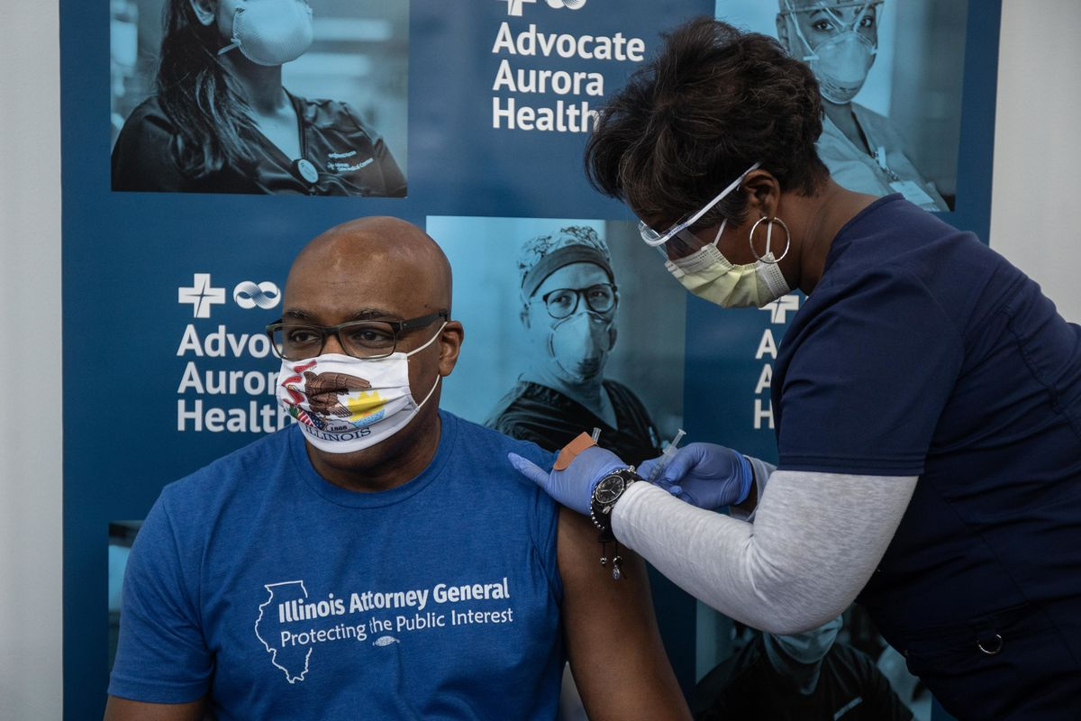 Nurse Carla Taylor-Wilson vaccinates Illinois Attorney General Kwame Raoul against COVID-19 at Advocate Health Care's vaccine clinic at Imani Village in the Cottage Grove Heights neighborhood on Friday.
