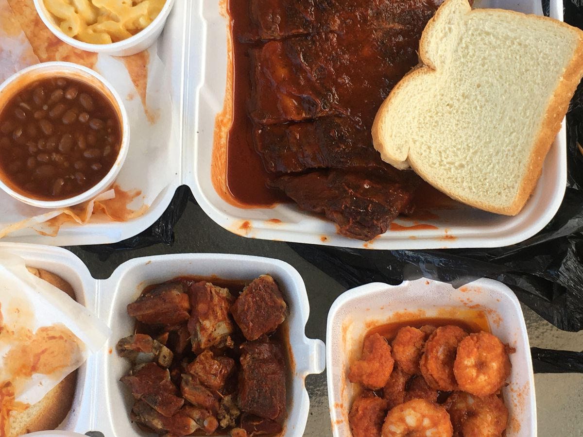 Ribs with white bread, rib tips, and fried shrimp in pools of red sauce in takeout containers.
