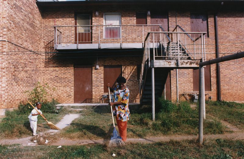 A woman and child use brooms to clean up lawn in front of a brick apartment building.