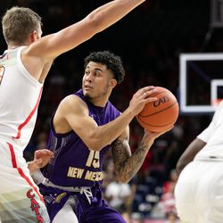 Western New Mexico's Jordan Enriquez, center, looks for an open teammate through an Arizona double-team during the Arizona-Western New Mexico University game in McKale Center on October 30 2018 in Tucson, Ariz.