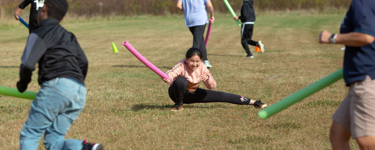 Fifth graders participate in a tag game using pool noodles to avoid contact.
