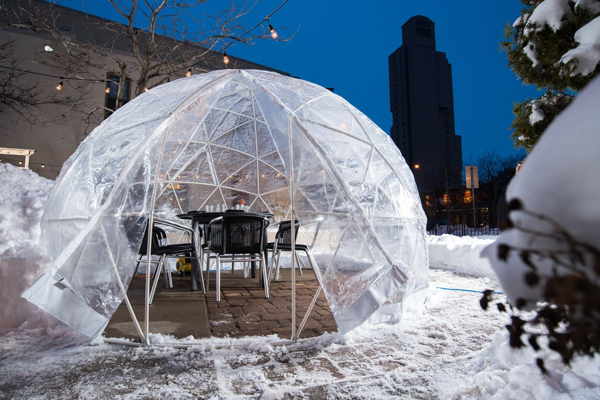 A plastic dome with a table set, surrounded by snow