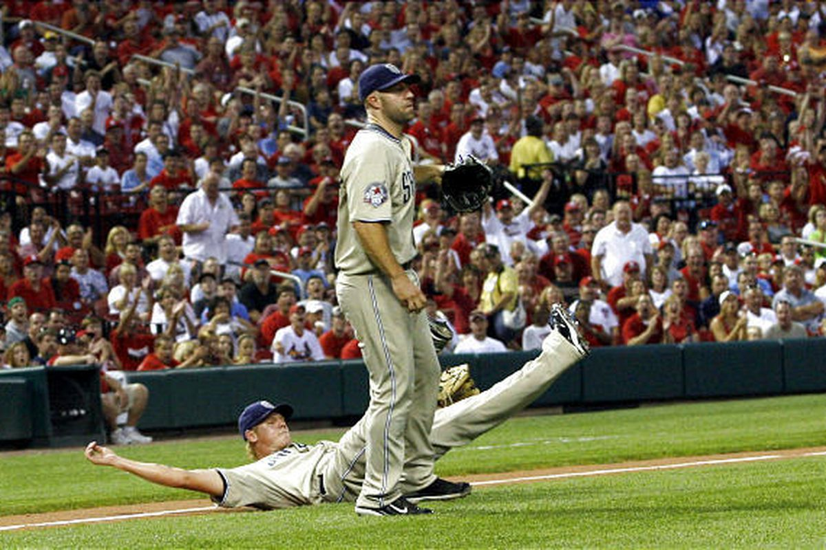 San Diego Padres relief pitcher Mat Latos lies on the ground after getting tangled up with third baseman Kevin Kouzmanoff while trying to make a play on a bunt.