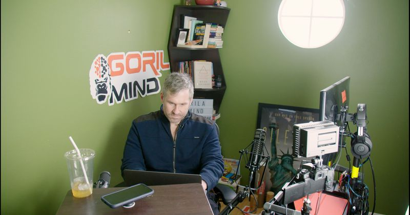 Mike Cernovich in a corner of a room in his house, with his computer and flanked by advertisements for a brain supplement.