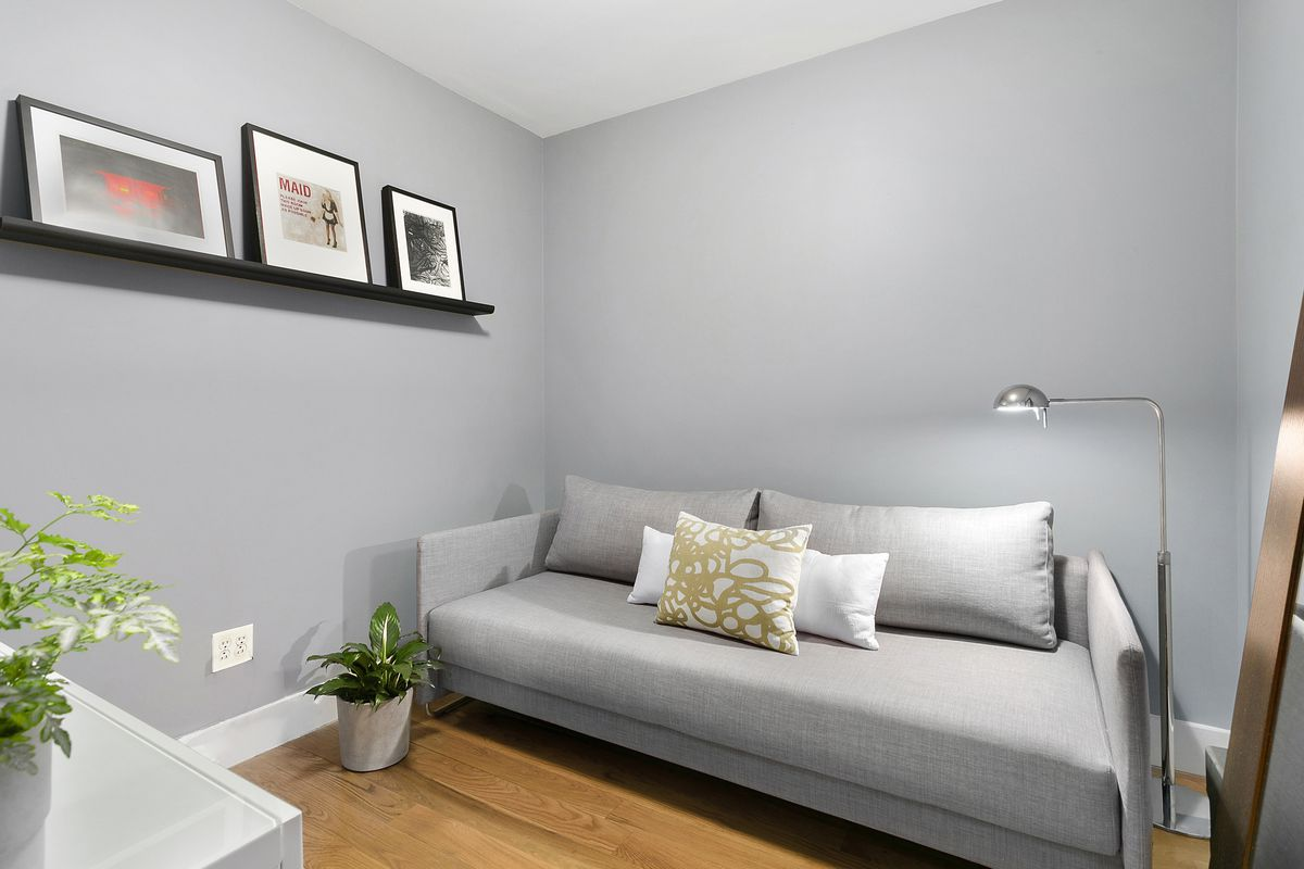 A room with a light grey couch, light grey walls, hardwood floors, and planters.