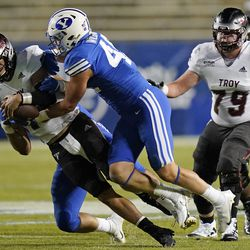BYU linebacker Payton Wilgar (49) sacks Troy quarterback Gunnar Watson, left, during the second half of an NCAA college football game Saturday, Sept. 26, 2020, in Provo.