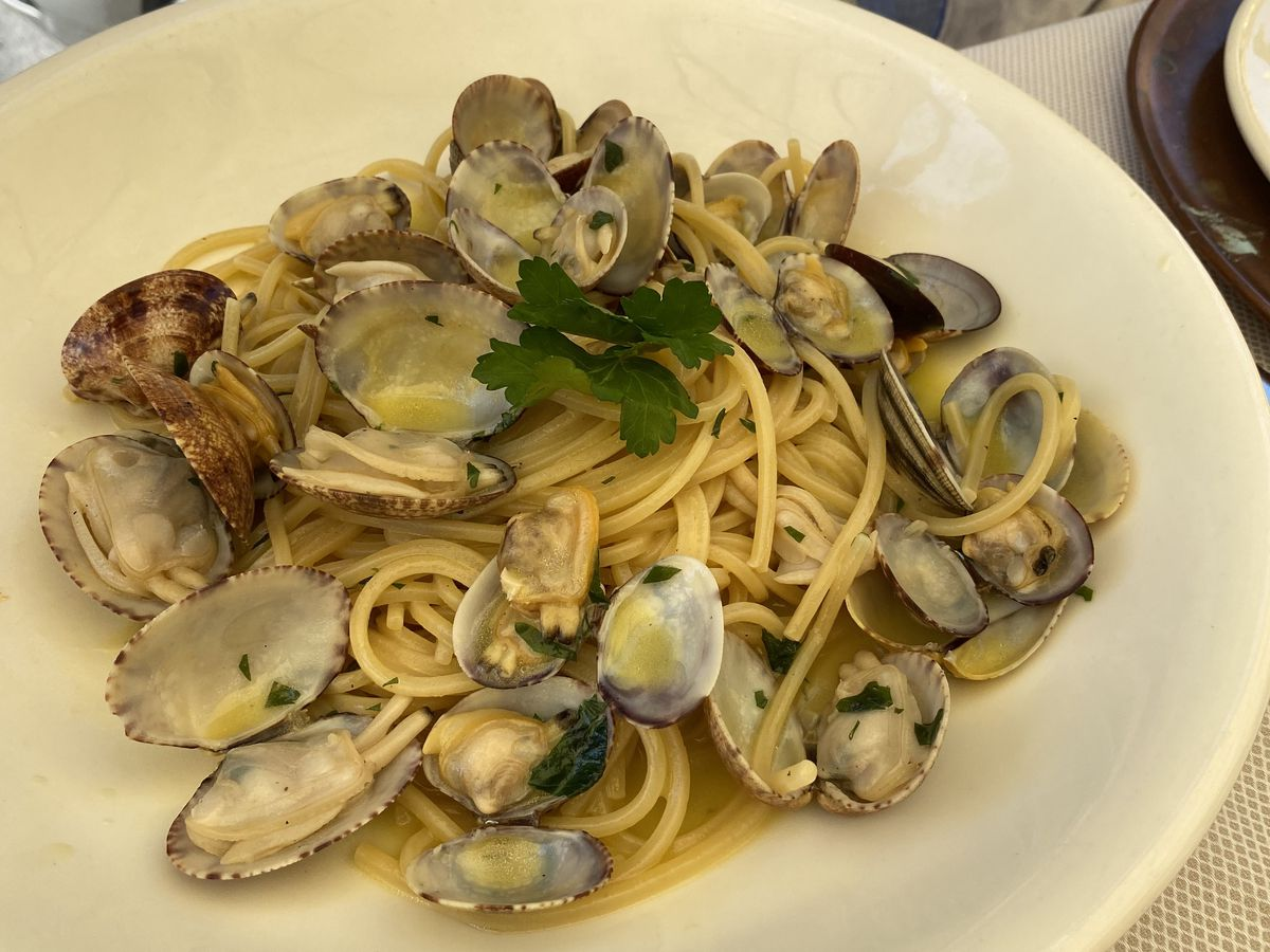 Spaghetti with clams in a shallow plate with a diner sitting behind