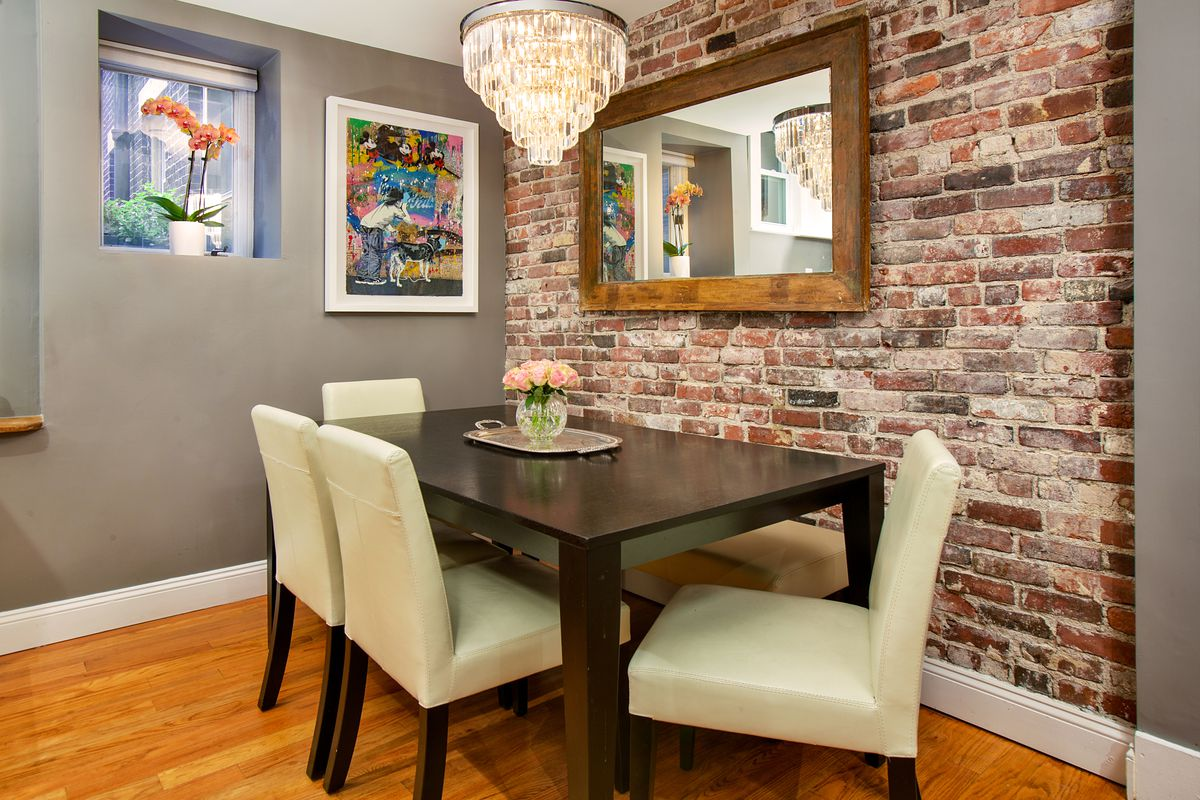 A small dining room area with a table and chairs next to an exposed-brick wall.