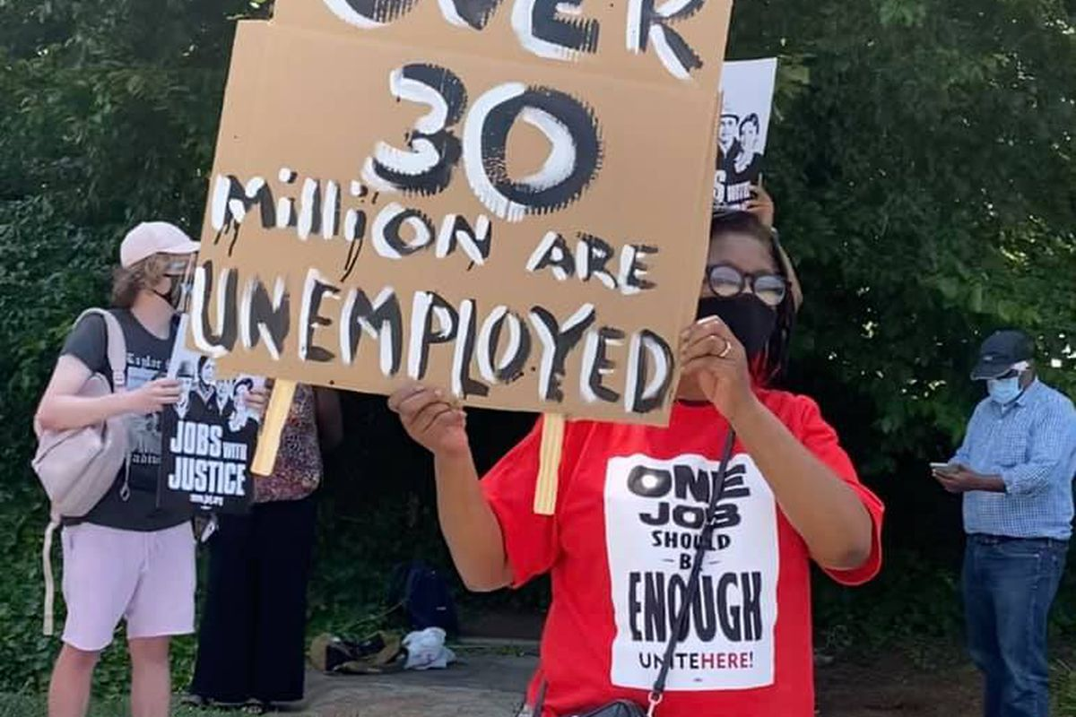 """a masked woman in a red shirt holding a sign that reads """"""""over 30 million are unemployed"""". Her shirt says """"one job should be enough"""""""