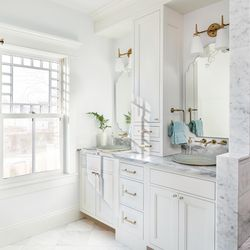 A double vanity topped with marble in the main bath holds partially recessed vessel sinks. Gold faucets and brass accents warm up the mostly white space. <em>Main bath fans: </em><a class=